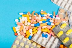Różne colourful pigułki i plastikowe paczki - bąble brogujący na błękitnym tle obrazy stock
