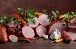 Różne kiełbasy i uwędzeni mięsa na drewnianym stole Fotografia Stock