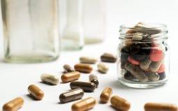 Różne pigułki i kapsuły w szklanym słoju na białym tle Fotografia Stock