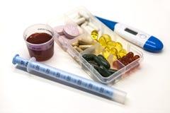 Różne pigułki, lekarstwa w pudełku dla leków z medycyną z strzykawką z termometrem na białym tła zbliżeniu i Zdjęcia Stock