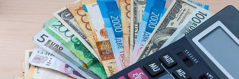 Różni banknoty różne cnoty kłamają fan na twój drewnianym biurku z kalkulatorem obraz royalty free