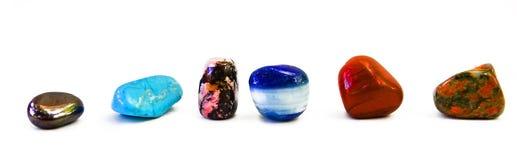 Różni barwioni kamienie w rzędzie odizolowywającym na bielu Fotografia Stock