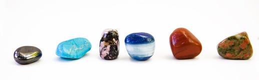 Różni barwioni kamienie w rzędzie odizolowywającym na bielu Obrazy Stock