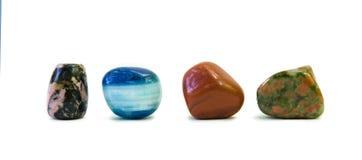 Różni barwioni kamienie w rzędzie odizolowywającym na bielu Fotografia Royalty Free