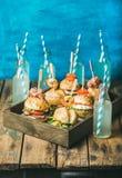 Różni hamburgery z kijami w drewnianej tacy i świeżej lemoniadzie Zdjęcie Stock