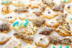 Różni kształty shortbread waniliowi Bożenarodzeniowi ciastka robić i dekorujący dzieciakami z lodowacenia czekoladowym ganache ko zdjęcie stock