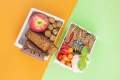Różni lunchy w dwa pudełek, pożytecznie i szkodliwych lunchach, Uwalnia przestrzeń dla teksta kosmos kopii obraz royalty free
