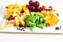 Różni rodzaje ser, pokrajać, czerwoni winogrona, orzechy włoscy, miód w pucharze, czerwony rodzynek, zielony ser, drewniany stoja Obrazy Royalty Free