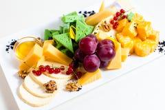 Różni rodzaje ser, pokrajać, czerwoni winogrona, orzechy włoscy, miód w pucharze, czerwony rodzynek, zielony ser, drewniany stoja Obrazy Stock