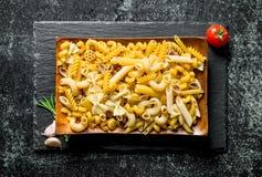 R??ni rodzaje surowa pasta na talerzu z pomidoru i czosnku cloves fotografia royalty free