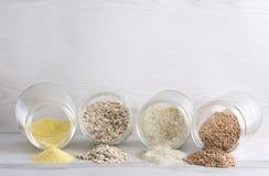 Różni rodzaje zboże w szklanym słoju Rozsypiska zboża na whiye kuchennym stole przeciw jaskrawej ścianie, opróżniają przestrzeń d zdjęcie stock
