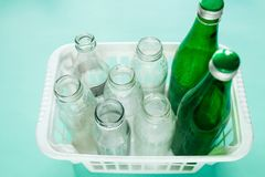 Różni szklanej butelki odpady gotowi dla przetwarzać w białym koszu na zielonym tle Odpowiedzialność społeczna, ekologii opieka, fotografia royalty free