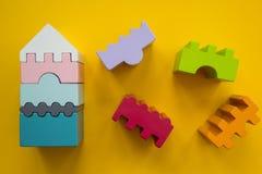Różnobarwni drewniani bloki - mieści odosobnionego na żółtym tle zdjęcia stock