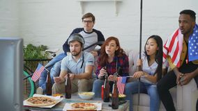 Różnorodna grupa ogląda hokejowego mistrzostwo na TV wpólnie rozwesela up przyjaciół sportów fan z usa flaga państowowa zbiory wideo