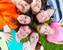 Różnorodna grupa przyjaciele na zewnątrz lying on the beach na gazonie Zdjęcie Stock