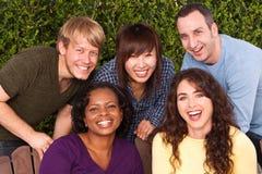 Różnorodna grupa przyjaciele siedzi outside obraz royalty free