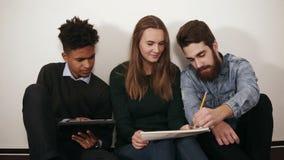 Różnorodna grupa ucznie lub młoda biznes drużyna pracuje na projekcie Siedzą na działaniu z i podłoga zdjęcie wideo