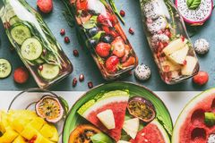 Różnorodna kolorowa natchnąca woda w butelkach z owoc jagodami, ogórek, ziele z składnikami na stołowym tle, odgórny widok Obraz Stock