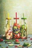 Różnorodna kolorowa natchnąca woda w butelkach z owoc jagodami, ogórkiem, ziele i napój słoma z składnikami na stole, Obraz Royalty Free