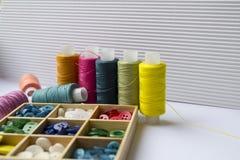Różnorodne barwione nici z odziewają guziki w drewnianym pudełku na wh zdjęcia stock