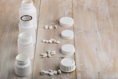 Różnorodne białe plastikowe pigułek butelki i rozsypisko leki Zdjęcie Stock