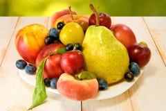 Różnorodne dojrzałe owoc na talerzu na zamazanym tle Zdjęcie Stock