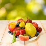 Różnorodne dojrzałe owoc na talerzu na zamazanym tle Zdjęcie Royalty Free