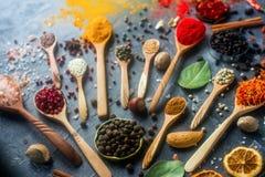 Różnorodne indyjskie pikantność w łyżkach, metali pucharach, ziarnach, ziele i dokrętkach na zmroku kamienia stole drewnianych i  Obrazy Royalty Free