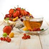 Różnorodne jagody i filiżanka herbata na drewnianym stole Obrazy Stock