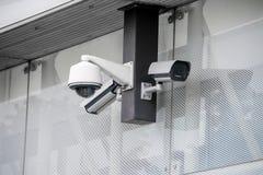 Różnorodne kamery bezpieczeństwa przy biurową szklaną budynek powierzchownością obrazy stock