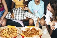 Różnorodne kobiety siedzi na leżanki łasowania pizzy wpólnie zdjęcia stock