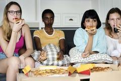 Różnorodne kobiety siedzi na leżanki łasowania pizzy wpólnie zdjęcie royalty free