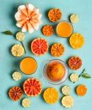 R??norodne kolorowe cytrus owoc przyrodnie z sokiem w szk?ach na b??kitnym tle, odg?rny widok Mieszkanie nieatutowy Zdrowy Styl ? obrazy stock