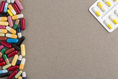 Różnorodne kolorowe kapsuły i pigułki na brown rzemiośle tapetują Zdjęcia Royalty Free