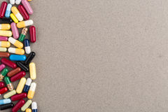 Różnorodne kolorowe kapsuły i pigułki na brown rzemiośle tapetują Zdjęcie Royalty Free