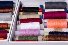 Różnorodne stubarwne używać szwalne nici w pudełku, brogującym w a Zdjęcie Stock