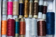 Różnorodne stubarwne używać szwalne nici w pudełku, brogującym w a Fotografia Stock