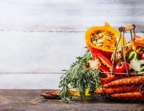 Różnorodnej jesieni warzyw sezonowi organicznie składniki: bania, marchewka, papryka, pomidory, imbir w koszu na drewnianym kuche fotografia royalty free
