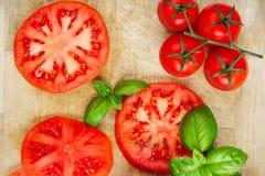 Różnorodni Świezi pomidory z basila liściem na tnącej desce, widok zdjęcie royalty free