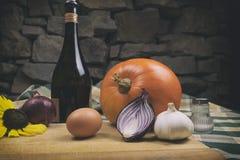 Różnorodni świezi rolni warzywa na drewnianym stole i tablecloth z kamiennej ściany tłem w zmroku Butelka wino z słonecznikiem Obrazy Stock
