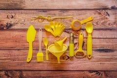 Różnorodni żółci kuchenni naczynia na drewnianym tle, odgórny widok obrazy stock
