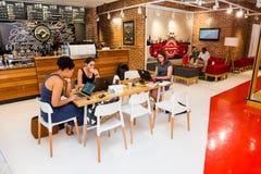 Różnorodni Żeńscy klienci używa internet w sklepie z kawą zdjęcie royalty free