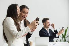 Różnorodni żeńscy koledzy śmia się mieć zabawę z smartphone wewnątrz fotografia stock
