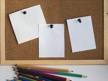 Różnorodni barwioni ołówki na tle korkują deskę zdjęcie stock