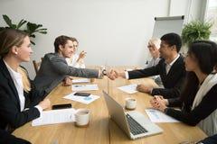 Różnorodni biznesmeni trząść ręki po podpisywać kontrakty przy gro zdjęcie stock