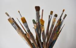 Różnorodni brudni farb muśnięcia w czarnej filiżance odizolowywającej na bielu obraz stock