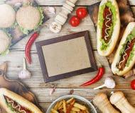 Różnorodni fastów food naczynia na łomota stole w centrum i - pusta rama dla teksta dla menu lub Hamburgery, hot dog, Frenc Obraz Stock