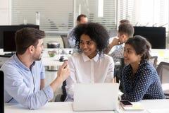 Różnorodni koledzy dyskutuje online projekt przy miejsce pracy obrazy stock