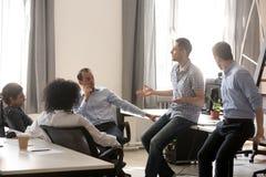 Różnorodni koledzy opowiada na biznesowym szkoleniu z trenerem obraz royalty free