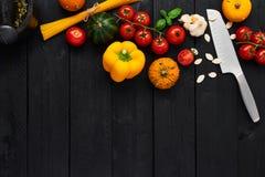 Różnorodni kulinarni składniki z moździerzem i nożem na czarnym woode fotografia royalty free